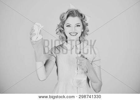 Pinup woman hold soup bottle, duster. Cleaning, retro style, purity. Housekeeper in uniform with clean spray, duster. Retro woman cleaner on grey background. Cleanup, cleaning services, wife, gender. poster