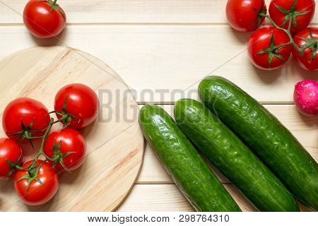 Fresh Organic Food Ingredients On Kitchen Wooden Table. Red Cherry Tomatoes, Green Cucumbers And Rad