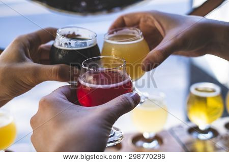 Friends Toasting With Beer At A Bar During Happy Hour.  Cheers!