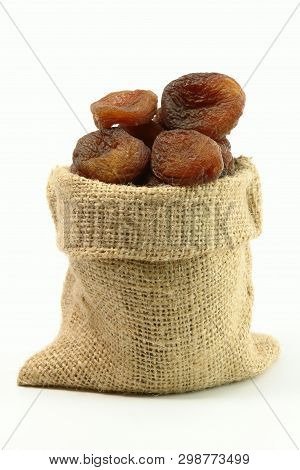 Stack Of Sundried Apricots In Gunny Bag (isolated On White Background)