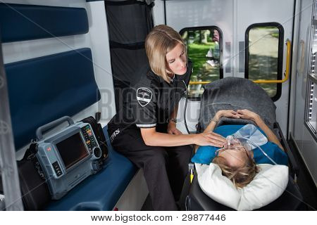 Female EMT worker tending to ill senior patient, listening to heart rate with stethoscope
