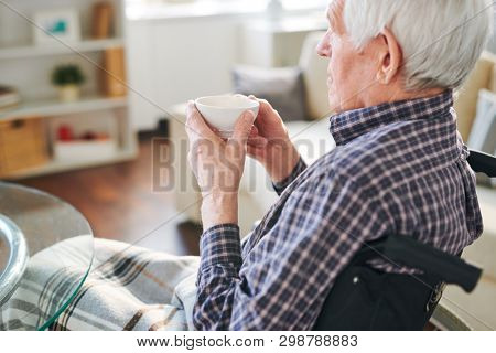 Handicapped senior man in wheelchair holding cup of tea while having rest after breakfast at home
