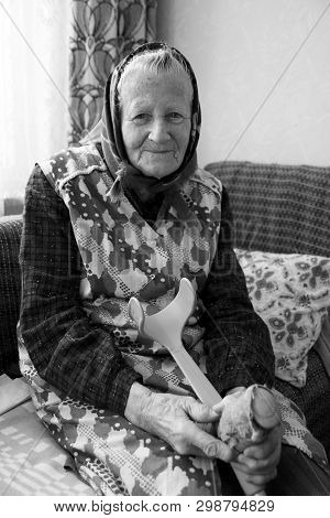 A Happy, Smiling Old Woman, Grandmother, Senior Sitting On The Couch, At A Cozy Home. Middle Europea
