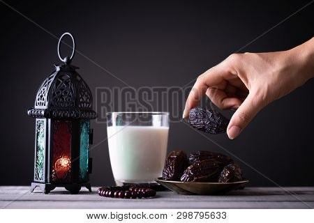 Ramadan Food And Drinks Concept. Woman Hand Reaches Out To A Plate With Date With Ramadan Lantern Wi