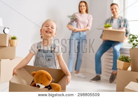 Happy young family are moving to new apartment. Parents and daughter with boxes.