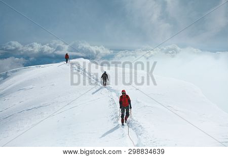 A Group Of Mountaineers Climbs To The Top Of A Snow-capped Mountain. Climbers Are Hiking On Mountain