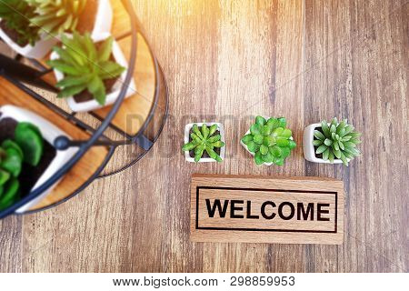 Warm Welcome Sign For Business Concept. Wooden Welcome Sign On Table Decorate With Little Cactus And
