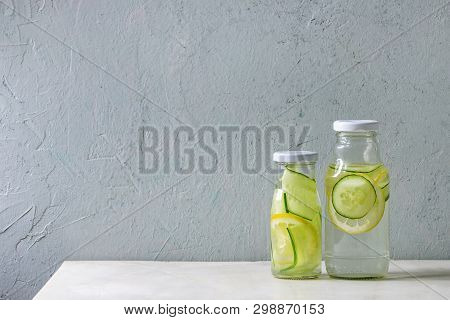 Summer Drinks Theme. Two Glass Bottles With Lemon And Cucumber Infusion Sassy Water On White Marble