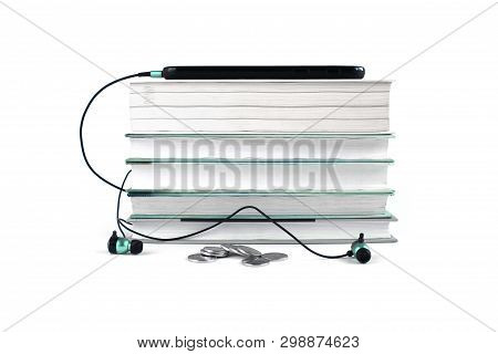 Concept Of Cheap Audio Books. Blue Headphones And Mobile On The Stack Of Books. White Background Wit