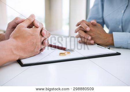 Husband And Wife Are Reading Divorce Agreement And Signing Decree Of Divorce (dissolution Or Cancell