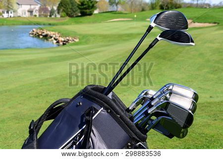 A set of golf clubs standing in a fairway on a scenic golf course with a lake and the green behind them poster
