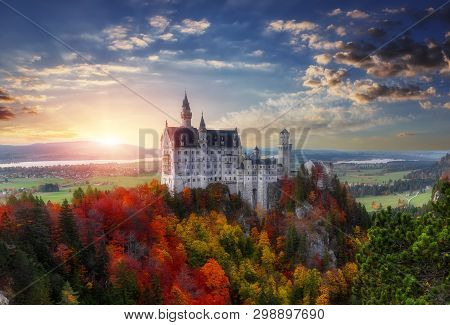 Tipical Postcard. Majestic Neuschwanstein Castle During Sunset, With Colorful Clouds Under Sunlight.