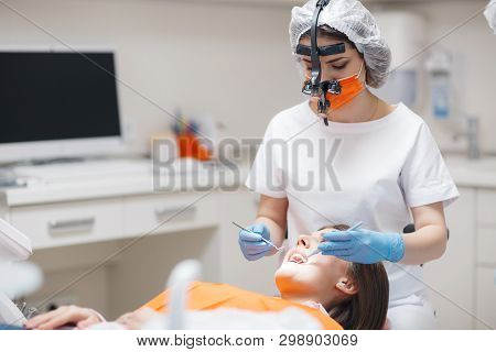 Dental Clinic. Reception, Examination Of The Patient. Teeth Care. Young Woman Undergoes A Dental Exa