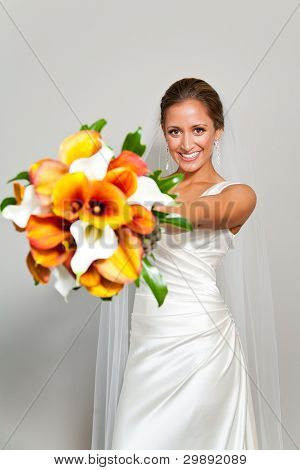 Bride Holding Her Bouquet In Front Of Her Against A White Wall