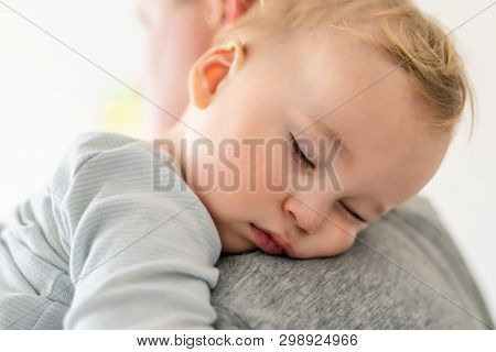 Close-up Portrait Of Cute Adorable Blond Caucasian Toddler Boy Sleeping On Fathers Shoulder Indoors.