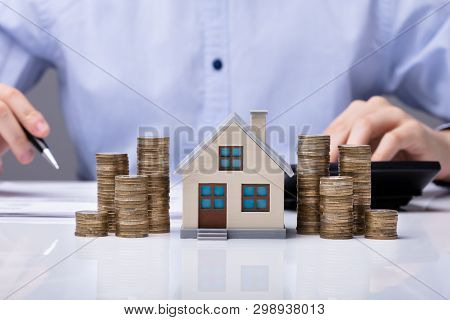 House Model And Stacked Coins On Desk In Front Of Businessperson Working On Document