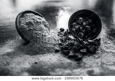 Popular Indian & Asian ayurvedic organic herb musli or Chlorophytum borivilianum or Curculigo orchioides or kali moosli in a clay with its powder in another bowl on wooden surface. poster