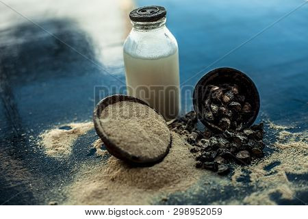 Popular Indian & Asian ayurvedic organic herb musli or Chlorophytum borivilianum or Curculigo orchioides or kali moosli in a clay on wooden surface with a transparent glass bottle filled with milk. poster