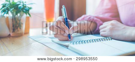 Woman Hand Is Writing On A Notepad With A Pen.web Banner.