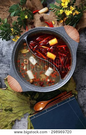 Spicy Red Oil And Clean Soup Hotpot In A Ceramic Pot