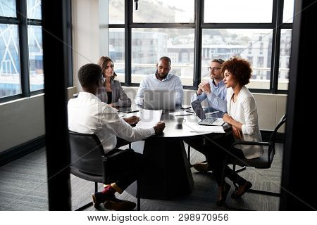 Corporate business colleagues talking in a meeting room, seen from doorway