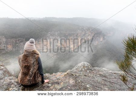 Female Dressed In Warm Winter Attire Sitting On The Cliff Ledge Looking Out Into The Misty Fog Fille