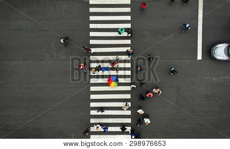 Aerial. People Crowd On Pedestrian Crosswalk. Zebra Crossing, Top View. One Person From Crowd Holds