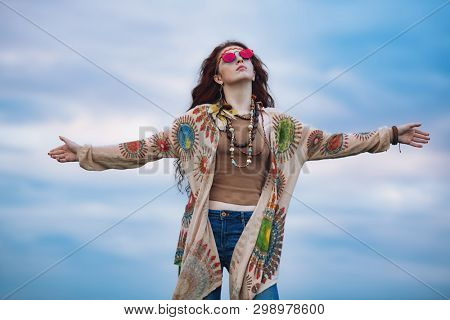 A portrait of a fashion female model against the sky in a coutryside. Contemporary bohemian style. Spirit of freedom. Fashion shot. Bohemian, bo-ho style.