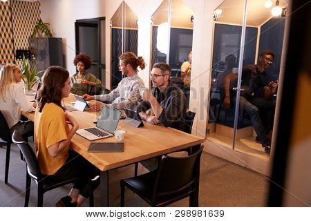 Creative colleagues sitting at a table socialising in their office canteen