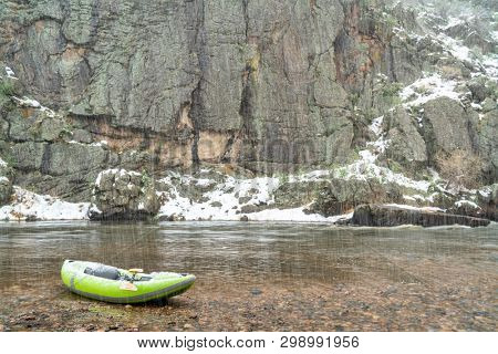 inflatable whitewater kayak with a paddle on shore of mountain river in springtime snowstorm - Poudre River in Colorado