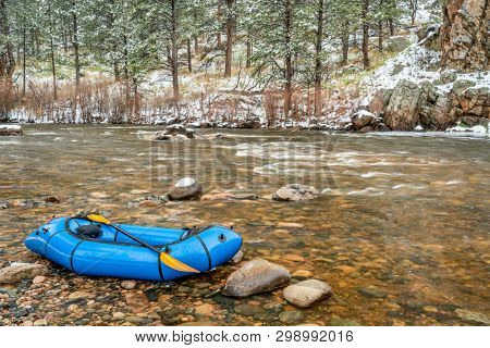 inflatable packraft (one-person light raft used for expedition or adventure racing) with a paddle on shore of mountain river in springtime snowstorm - Poudre River in Colorado