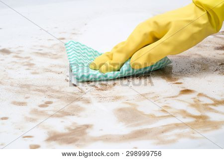 Hand Wearing A Glove Wiping Spills On A Counter Top Or Floor With A Cloth Or Rag