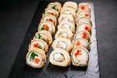 Tempura maki. Japanese sushi rolls set on black slate. Japanese traditional fusion food style, restaurant menu, degustation, buffet poster