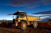 Huge auto-dump yellow mining truck night shot and excavator poster