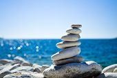 Close-up of white pebbles stack over blue sea poster