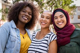 Group of three happy multiethnic friends looking at camera. Portrait of young women of different cultures enjoying vacation together. Smiling islamic girl with two african american friends outdoor.