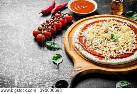 Preparation Pizza. Rolled Out Dough With Tomato Paste, Cheese And Cherry Tomatoes. On Dark Rustic Ba