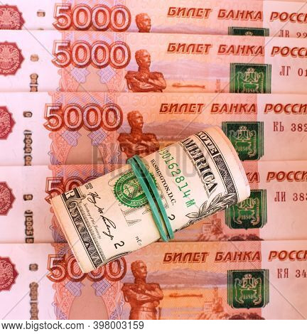 Rolled Up American Dollars And Banknotes Of 5000 Russian Rubles. American Sanctions. Money Backgroun