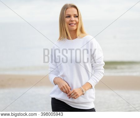 Young woman wears white blouse in summer or autumn time. Blond woman stands in front of camera on beach, outdoor. Fashion mockup with copy space.