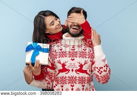 Attractive Couple Dressed In Christmas Sweaters Woman Covering Her Boyfriends Eyes Over Blue Backgro