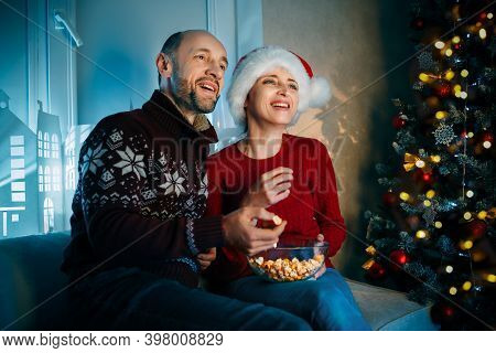A Husband And His Wife Enjoy Popcorn On Christmas Eve While Watching Tv And Laughing Loudly While Wa