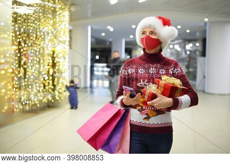 A Woman Wearing A Protective Mask Holds Gift Boxes And Shopping Bags At A Shopping Center While Shop