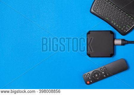 Tv Box And Remote Controls For Ip Tv And Digital Video Content On A Blue Background