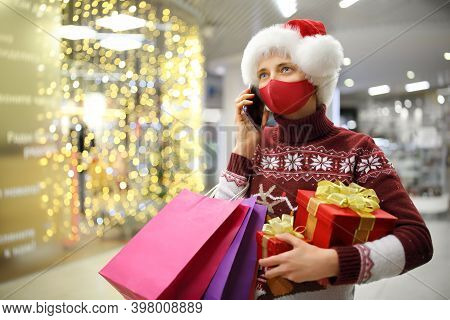 A Woman In A Protective Mask Holds Gift Boxes And Gift Bags, Talking On The Phone In A Shopping Cent
