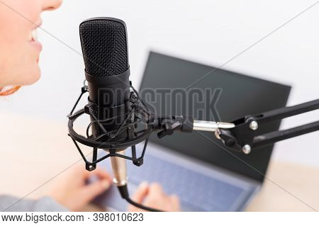 Rear View Of Woman Broadcasting Online Radio On Laptop. The Girl Is Recording A Podcast On Her Chann