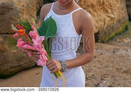 The Bride Holds A Beautiful Pink And Green Wedding Flowers Bouquet In Her Hands On Beach Background.