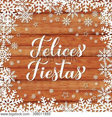 Felices Fiestas Calligraphy Hand Lettering On Wood Background With Snowflakes. Happy Holidays In Spa