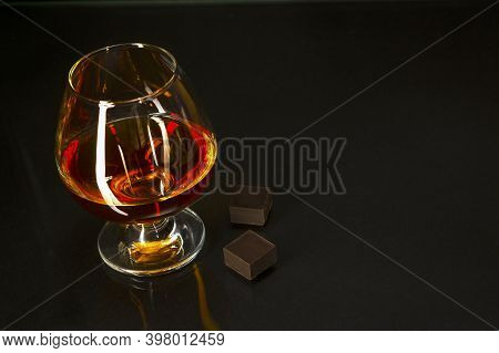 Cognac Glass And Chocolate On Black Background. Brandy Glass. Cognac Glass. Whiskey Glass. Cognac Fr