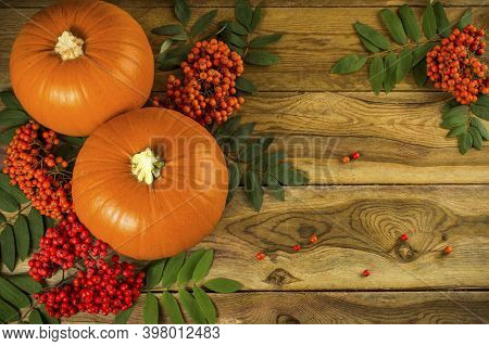 Fall, Pumpkins, Rowan Berries And Leaves On Wooden Background