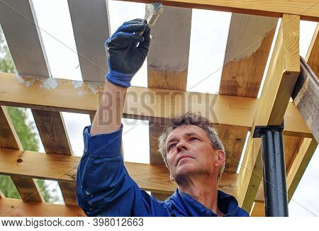 A Worker Paints The Wooden Roof Of His House, The House Is Under Construction. Renovation, Extension